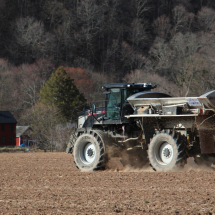 Spreading chicken manure on fields before they were seeded with oats and clover.